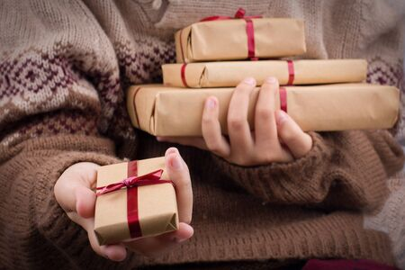 Hand holds out a gift box. Girl in a knitted sweater holds a stack of gift boxes in a brown craft paper. 스톡 콘텐츠