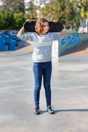 Girl teenager with a skateboard. Beautiful fashionable skateboarder in jeans and a hoodie on ramp. Zdjęcie Seryjne