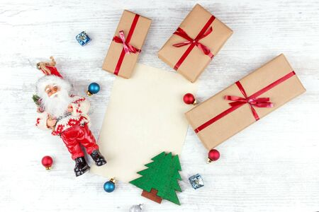 Christmas and New Year background with gift boxes, Santa and sheet of paper