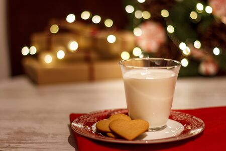Gingerbread cookies and a glass of milk for Santa Claus on the background of Christmas garland and a wreath of pine needles