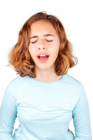Beautiful young girl with curly hair sings with open mouth. Yawning girl