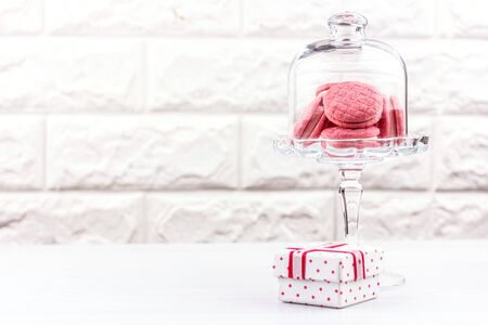 Pink macaroon cookies in a crystal vase and a gift box