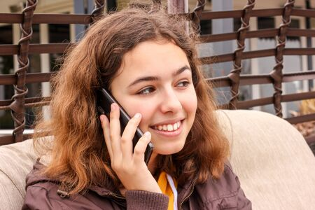 Cute cheerful teenager girl talking by the phone and smiling