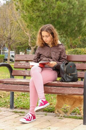 Cute serious teenager girl reading book sitting on the bench outside at the park 版權商用圖片