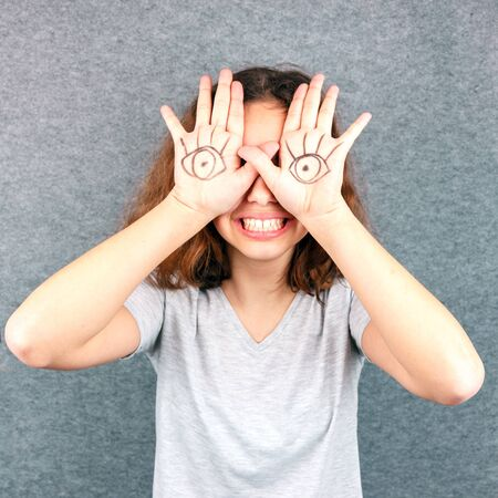 Funny girl with eyes drawn on her palms. April Fools joke
