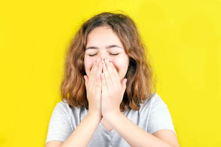 Portrait of funny curly teenager girl laughing and closing face with hands