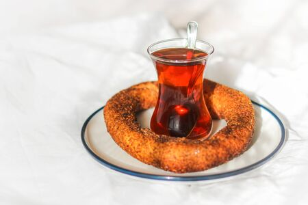 Breakfast in bed. Turkish tea in traditional glass and simit sesame bun