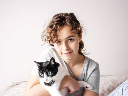 Beautiful curly teenager girl in the bed hugs a cat. Pet love. Animal care