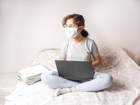Teenager girl with medical mask is studying online on her bed and looking to the window. 版權商用圖片