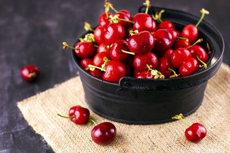 Fresh cherry on black wooden table. Ripe sweet berries in the droplets of water