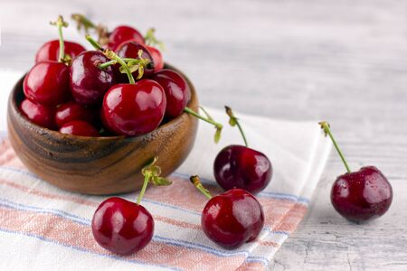 Fresh cherry on the white wooden table. Ripe sweet berries in droplets of water 版權商用圖片 - 146484532