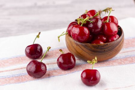 Fresh cherry on the white wooden table. Ripe sweet berries in droplets of water
