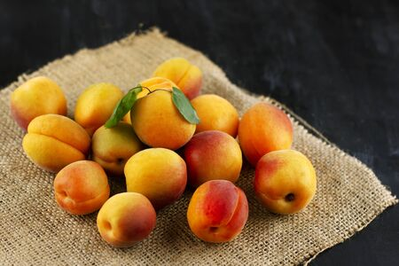 Fresh apricot on a sackcloth on black wooden table. Ripe sweet berries in droplets of water