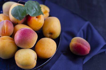 Fresh apricot on a dark silk fabric. Ripe sweet berries in droplets of water 版權商用圖片
