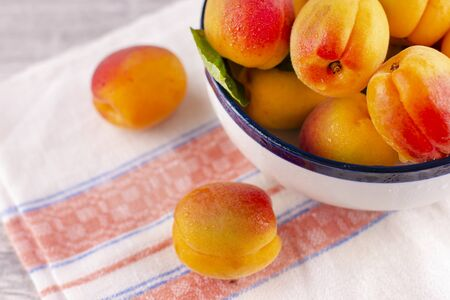 Fresh apricot on a white wooden table. Ripe sweet berries in droplets of water Zdjęcie Seryjne