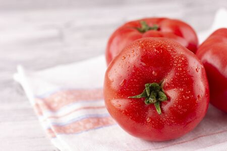 Large pink tomatoes with droplets of water. Fresh ripe vegetables on a wooden table Zdjęcie Seryjne