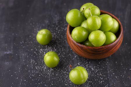 Unripe salty green plums on black wooden table 版權商用圖片
