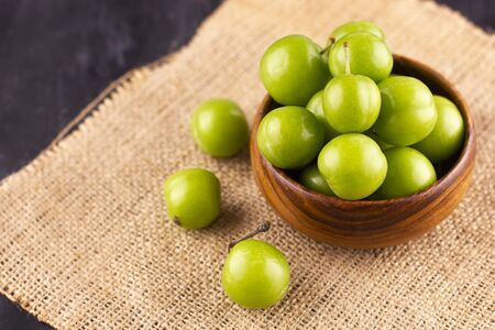 Unripe green plums on black wooden table