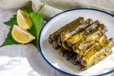 Traditional turkish meal - Yaprak dolma. Grape leaves stuffed withrice and spices. Served with olive oil and fresh lemon