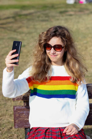 Pretty smiling teenager girl taking selfie. Happy curly young girl wear rainbow sweater