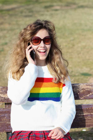 Pretty smiling teenager girl talking by phone. Happy curly young girl wear rainbow sweater
