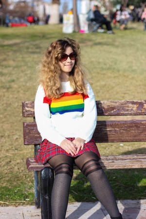 Pretty smiling teenager girl . Happy curly young girl wear rainbow sweater