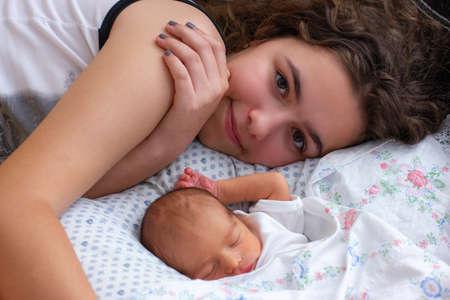 Very young mother lays on bed near her sleeping newborn baby 版權商用圖片