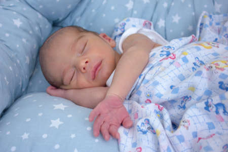 Sweet calm newborn baby sleeping on the bed with hand under cheek 版權商用圖片