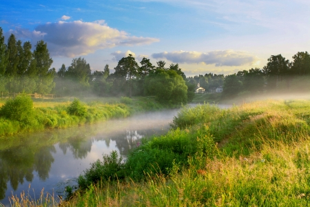 summer sunrise over the river with a fog