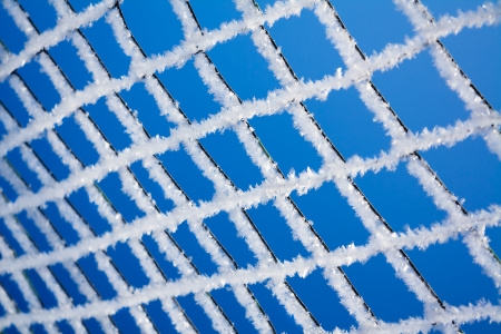 snowbanks: abstract winter background from a lattice against the blue sky Stock Photo