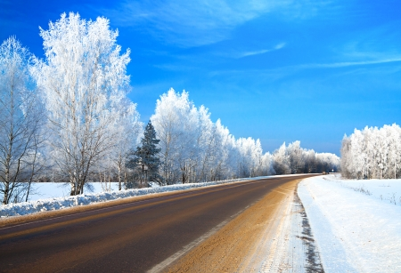 winter landscape with the road the forest and the blue sky Stock Photo