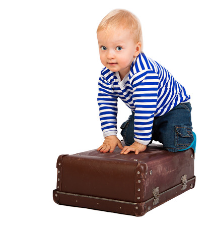 the beautiful little child  with a suitcase  isolated on a white background photo