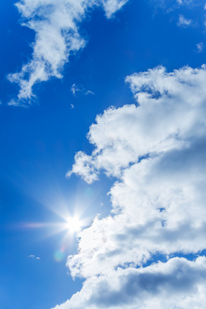 background from the blue sky with white clouds and the sun photo