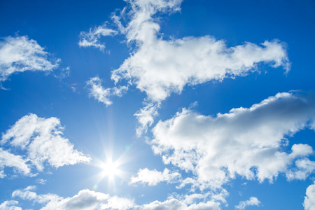 the blue sky with white clouds and the sun photo