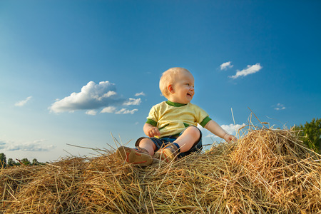 the little child smiling against the blue sky photo