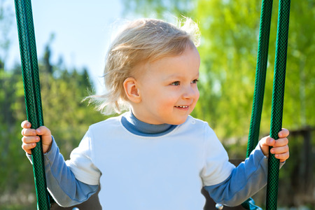 the happy child swinging on a swing photo