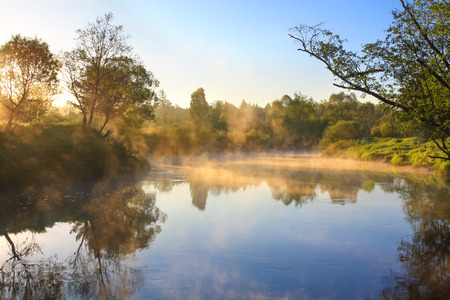 rural landscape with sunrise over the river and fog photo