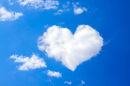background from the blue sky with a white cloud in the form of heart photo