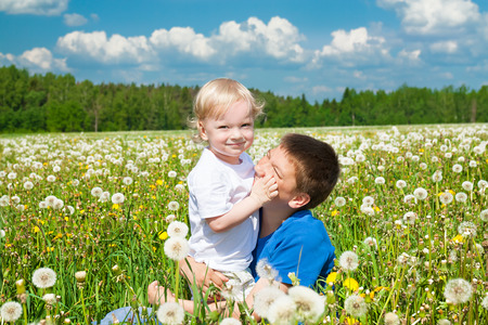 two children plays on a green meadow photo