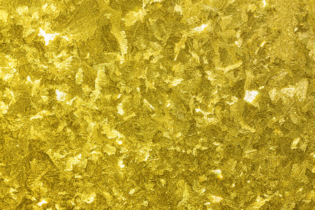 abstract shiny gold  yellow background from a frosty pattern on glass photo