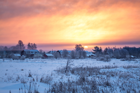 beautiful winter rural landscape with village, sunrise and fog