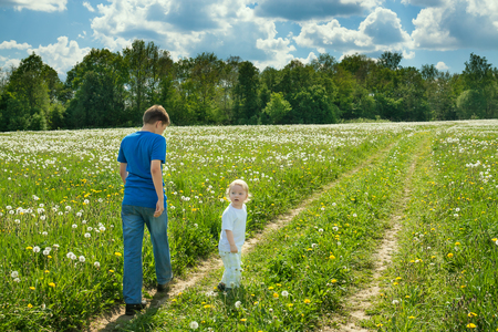 two children boys play on a summer meadow. family activity leisure in spring park Stock Photo