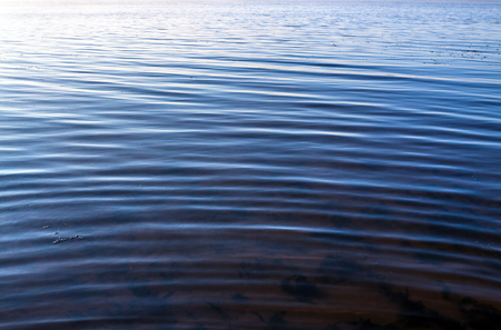 non: abstract blue background of water surface on with waves. rural landscape with river. sunrise on river. Russia Volga