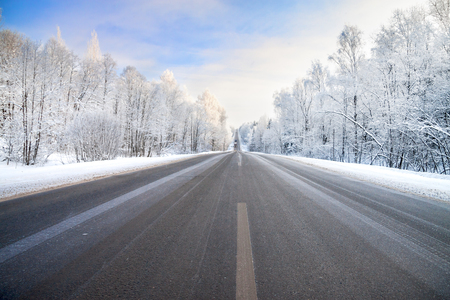 beautiful winter landscape with asphalt road,forest and blue sky.  frozen wintry day and path drive
