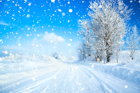winter landscape with road, forest and blue sky. wintry path. frosty sunny day. snowy winterly landscape. Stock Photo