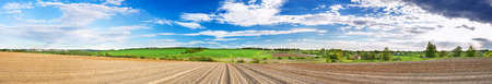 spring panorama of landscape with ploughed field, hills, blue sky with white clouds. panoramic view Stock Photo