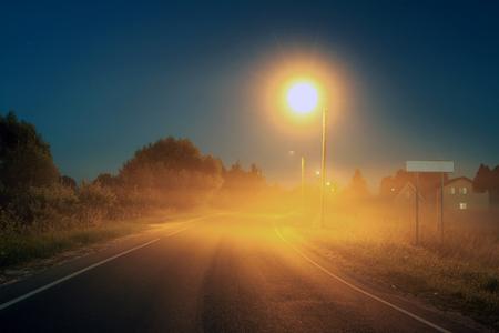 Autumn landscape with night road and fog. Street lights illuminate  road