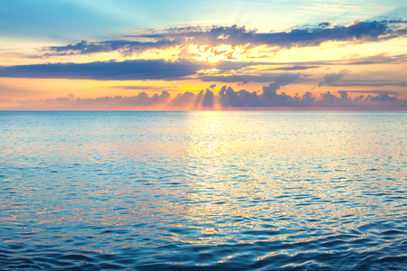beautiful sea landscape with a sunset. evening sky with clouds and sunshine over ocean. sun rays shine break through clouds 版權商用圖片 - 117765170