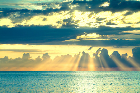 beautiful sea landscape with a sunset. evening sky with clouds and sunshine over ocean. sun rays shine break through clouds 版權商用圖片 - 117765173
