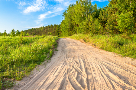 beautiful spring rural landscape with road and forest. countryside sandy path through forest and meadow 版權商用圖片 - 121359816